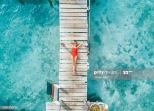 Aerial shot of womann relaxing in a water bungalow